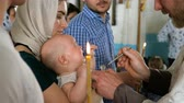 doop : Kiev, Ukraine, May 2019: - Newborn baby baptism. Orthodox priest baptizes a child with holy water. Mothers hands holding baby. Sacrament of baptism. Child and god. Candle for christening.