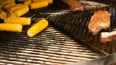 pannocchia : Corn on the cob and pork steaks are roasted on a rotating grill or barbecue. Motion blur.