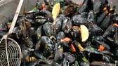 palourde : Large metallic pan preparing mussels. Fresh mussels on cooking pan. Seafood barbecue outdoors. Street trading mussels and shells.