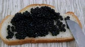 キャビア : Preparation of sandwiches with black caviar. Black sturgeon caviar is smeared with a kitchen knife on a slice of white bread. Delicious culinary delicacies. Expensive luxury food.
