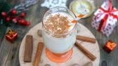 spiked : Homemade traditional christmas spicy hot drink eggnog with ground nutmeg, cinnamon in a glass, for funny christmas holiday. Rotates in a circle.