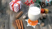 spiked : Preparation homemade traditional christmas spicy hot drink eggnog with ground nutmeg, cinnamon in a glass, for funny christmas holiday.