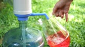 cruche : Human hand fills a transparent jug with cold water from a large bottle or cooler with a water pump. Against the background of green grass. Selective focus. Outdoors. Slow motion.