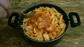 galinha : Homemade cooking. Red savory sauce with sliced chicken meat, is added into pasta and mixed in metal pan.