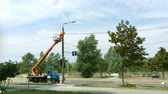 grue tour : Repair of city lighting. Worker electric changes a lamp or repairs equipment on a lamppost beside to the road. With a truck crane. Overall plan.
