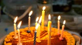 チョコレート : Beautiful delicious birthday cake with burning candles is on kitchen table. Maybe it was prepared for birthday celebration. Selective focus. Close-up. 動画素材