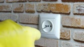 プラグ : Human hand in a rubber glove installs a socket on a brick wall in the house with a screwdriver. Selective focus. Close-up. 動画素材