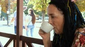Impressive senior Caucasian brunette woman drinking coffee in street cafe on city street. Outdoors. Close-up.