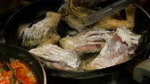 Homemade kitchen. River fish carp, cut into pieces, is fried in pan in cooking oil. Close-up.