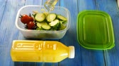 cruche : Human hands pour with cooking oil fresh salad, cucumber and cherry tomatoes in plastic lunch box. Nearby is plastic bottle of orange juice. Healthy vegetarian food concept. Top view.