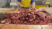 Worker cut up meat in meat factory
