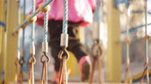 child walks on a suspension bridge on playground