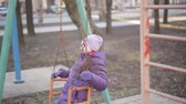 confident : a little girl swinging on a swing at the playground