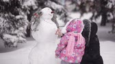 family values : parents and children playing in the snow. Mom and daughter sculpt of snow in the winter woods.