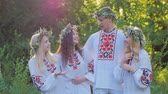 floral : a group of girls and boys in the Slavic national dress in the woods smiling and talking. The celebration of the summer equinox.