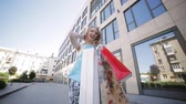 shoppingbag : A beautiful girl with bright packages near the shopping center enjoys her shopping. Stock Footage