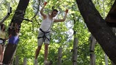 carbine : young people in safety equipment are obstacles on the road rope Stock Footage