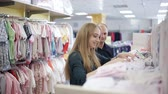 baby store : pregnant woman with her husband in a childrens clothing store. Happy family choose clothes for baby Stock Footage