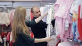 бутик : Young happy pregnant woman choosing newborn clothes at the baby shop store stock footage video
