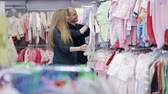 baby store : happy young family choose clothes for their unborn child. Pregnant woman in a store. Childrens goods store