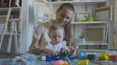 пластилин : Young attractive mother with cute little daughter. Mom and baby girl doing models by plasticine.