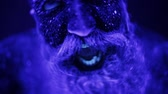 luxúria : An evil man with a beard in the ultraviolet light is frighteningly screaming. A terrible bearded man in ultraviolet light. Close-up of a face.