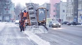 kluzký : Tractor cleaning the road from the snow. Excavator cleans the streets of large amounts of snow in city. Workers sweep snow from road in winter, Cleaning road from snow storm.
