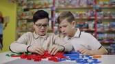 детский : Two teenagers in the childrens development center play constructor. Стоковые видеозаписи