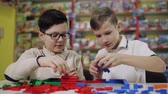 детский : Two boys use the constructor at the showroom table at the Mall.