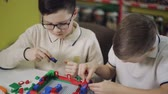 детский : Little children playing with lots of colorful plastic blocks indoor,.