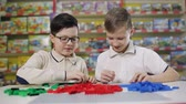 entellektüel : Two teenagers in the childrens development center play constructor. Stok Video