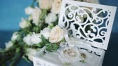 jewelry box : Wedding concept. Wedding rings in a wooden box handmade, surrounded by flowers on a turquoise background. Stock Footage