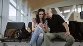 boarding pass : The guy and the girl in casual clothing looking at the tablet sitting on a black chairs in an airport waiting hall. People are discussing something looking on the gadget screen.