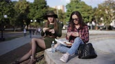 the digestion : Two girls hipster in the Park eating sandwiches and talking Stock Footage