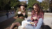 kaykay : Urban picnic in the Park. Two girls hipster talk and eat sandwiches. The holiday sandwich.