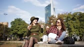 consumir : Two different and unusual women eat on the street sandwiches and fries. Vídeos