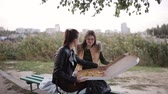 cena urbana : Two women eating pizza in a large box in the city sitting on a bench on the promenade
