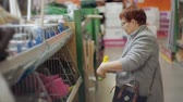 грабли : An elderly woman in a hypermarket in the Department tools chooses necessary equipment for the garden