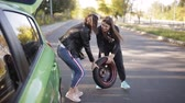 vida : Two women taking out spare wheel out of the car and rolling it on ground