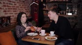 társult : A young couple chained together by handcuffs Breakfast in the cafe
