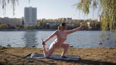 tilt : Beautiful girl in a tracksuit on the citys waterfront does yoga. Stock Footage