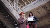 list : Woman engineer talking to a foreman on the construction site, solving organizational issues.
