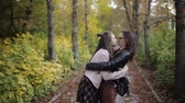 понимание : Mother and daughter a teenager walking, talking and hugging in autumn Park.