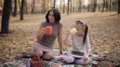 mother board : A cute mother and daughter are drinking tea while sitting on a plaid in a park. Little girl draws beefy on the board