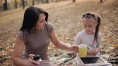 niania : A cute mother and daughter are drinking tea while sitting on a plaid in a park. Little girl draws beefy on the board