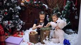 ziyafet : Two little girls at a Christmas tree prepare a gift for the grandmother Stok Video