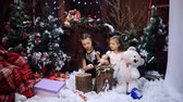 irmãs : Two little girls at a Christmas tree prepare a gift for the grandmother Stock Footage