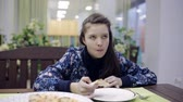 chew : girl eating pizza at a cafe. A teenager in a pizzeria is having supper