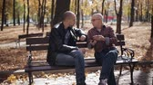 rogalik : Adult son of an elderly father teaches the smartphone in autumn Park on a bench. Wideo