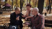 disputa : Family walk in the Park. The link between generations. Adult son talking with elderly parents in the autumn Park. Stock Footage